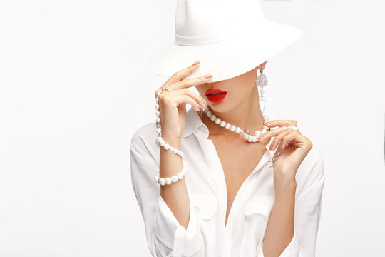 Beautiful girl in an elegant white hat and exquisite jewelry.
