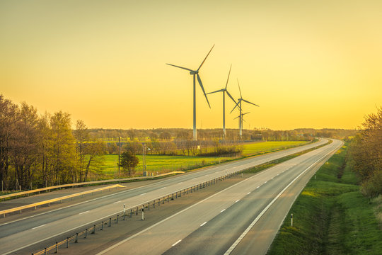 Picture of wind farm generators in the green field close to the road with cars at the sunset