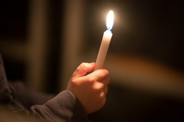 burning church candles in the hands of children on a dark background