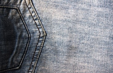 Background texture of blue faded denim jeans with pocket stitch lines