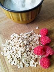 Fototapeta jogurt z malinami i płatkami owsianymi na desce drewinianej