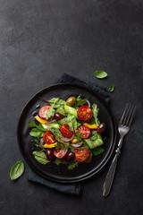 Fresh vegetable salad with tomato, cucumber, bel pepper and olives salad on black plate