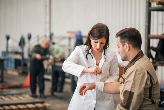 Beautiful female doctor examining factory worker.