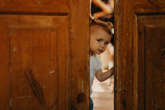 a pretty little girl hiding behind a large wooden door looking in the gap between them. Selective focus, noise effect