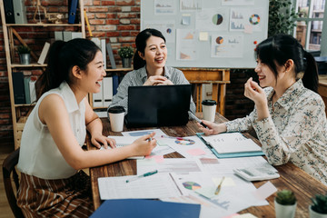 asian female businesspeople sitting together at office table working on a laptop and discussing documents. happy start up small business team partners having meeting with joy emotion in modern place