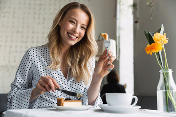Beautiful young blonde woman sitting at the cafe