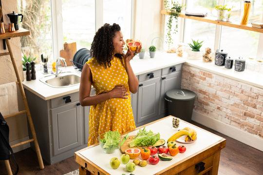 Happy pregnant woman smelling a grapefruit half.