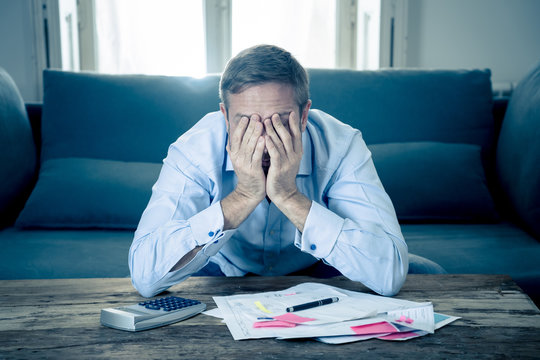 Upset man in stress paying bills counting finance with calculator bank papers expenses and payments