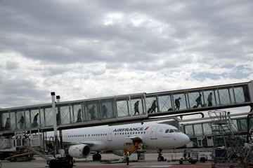 Passengers disembark from an Air France plane at the Paris Charles de Gaulle airport in Roissy