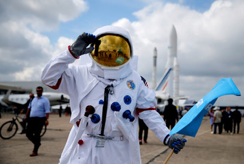 A man who works at Cobham Aerospace Communications company wears an astronaut suit at the 53rd International Paris Air Show at Le Bourget Airport near Paris