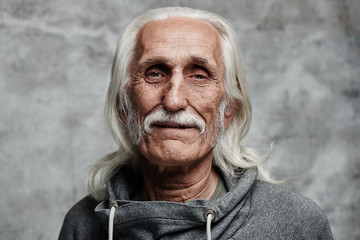 Portrait of aged gray haired Caucasian man pensioner. Cool grandpa with mustache and smiling kind face looking at camera on gray background