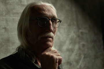 Aged gray haired Caucasian retired man thinking about life. Grandfather in glasses with mustache and thoughtful facial expression holds his chin, copy space