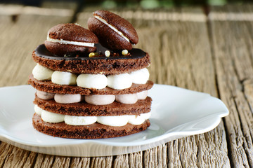 Baking homemade chocolate cake with biscuit, meringue and macaroons in white plate on wooden table. Festive sweet dessert birthday decoration macarons