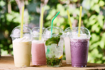 Refreshing soft colorful drinks, milk berry cocktail with cream, mojito, ice tea. Milkshake in plastic glass with straw in summer bar, nature background