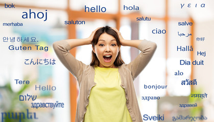 translation, education and people concept - happy asian young woman holding to her head over greeting words in different foreign languages