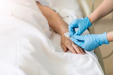 Closeup of a nurse inserting an IV into an elderly woman's hand