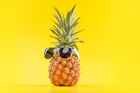 Creative pineapples with sunglasses isolated on yellow background, summer vacation beach idea design pattern, copy space, close up, blank for text