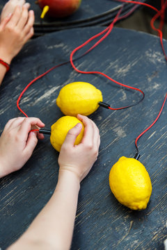 Image of lemons with red wires on black wooden table