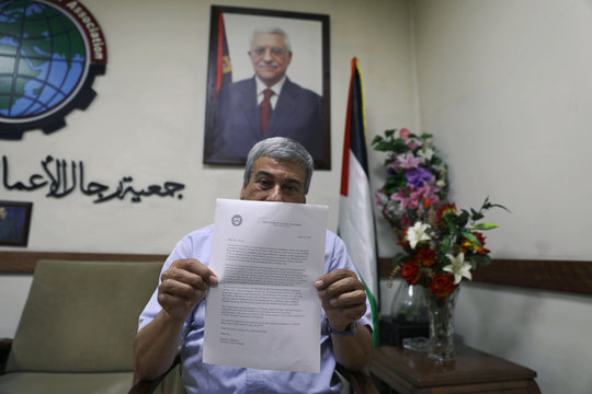 Palestinian businessman Abed Alkarim Ashour shows an invitation letter from the U.S. Department of the Treasury for a U.S.-led conference in Bahrain, in Gaza City