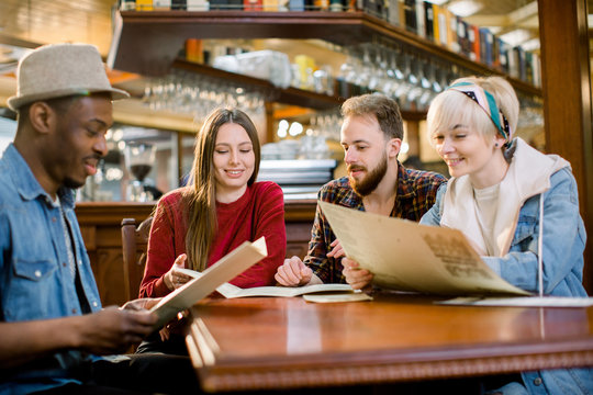 leisure, people and holidays concept - smiling young people in casual clothes reading menu at restaurant