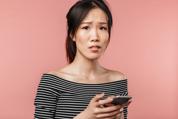Photo of frustrated asian woman dressed in basic wear looking unhappy while holding smartphone Fototapete