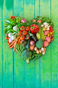 Herz aus Gemüse vor grünem Hintergrund aus Holz