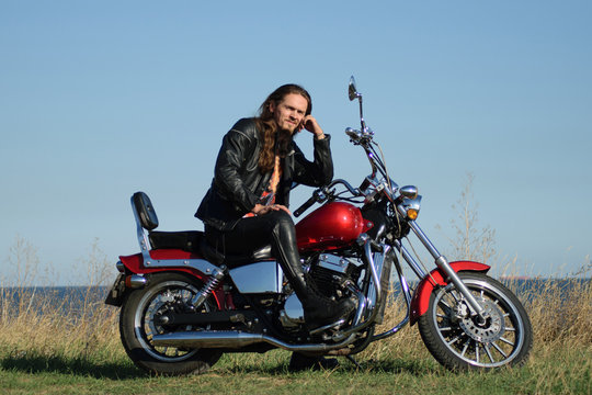 Handsome long-haired biker in the leather on red motorcycle against field and seashore. Brutal man in leather