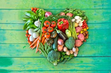 Herz aus Gemüse auf grünem Hintergrund aus Holz