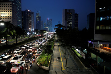 People walk on a pedestrian lane during a traffic jam at a business district in Jakarta