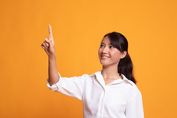 Asian woman touching the screen with  finger. Wall mural