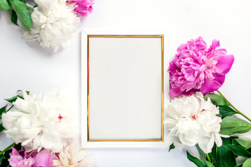 White and golden wooden frame decorated with peonies flowers. Mockup, top view, space