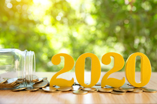Word 2020 put on coins and glass bottles with coins inside on green bokeh background.Savings New year Concept.