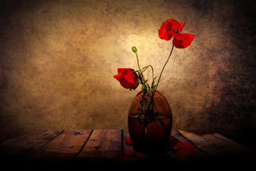 Vase with red field poppies