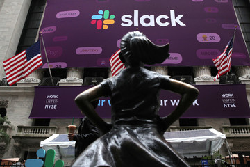 """The Slack Technologies Inc. logo is seen behind """"Fearless Girl"""" statue outside New York Stock Exchange (NYSE) during the company's direct listing in New York"""
