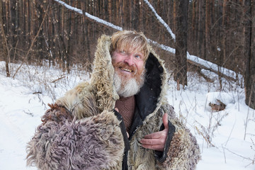 Bearded cheerful man in the winter forest.