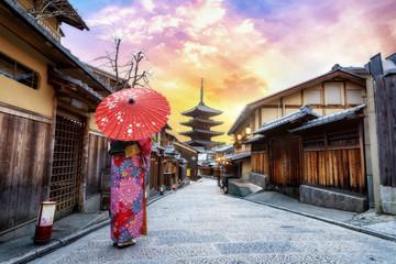 Young women wearing traditional Japanese Kimono with japan umbrella at Yasaka Pagoda and Sannen Zaka Street in Kyoto, Japa Wall mural