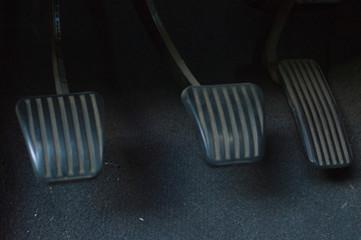 three manual car pedals: clutch, brake and accelerator
