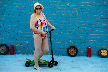 Elderly woman in striped swimsuit, sunglasses and elegant hat riding scooter against brick wall. Pensioner keeps health and looks great