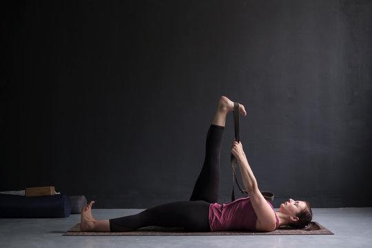 Woman working out using yogic belt, lying in yoga Supta Padangushthasana, One Leg Lift exercise