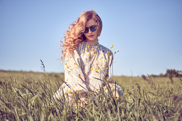 Wall Mural - Fashion portrait. Carefree woman walking at sunny grass field in stylish dress. Young Beautiful Cheerful blonde Model girl enjoy sunlight summer, fashionable outfit. Outdoor, authentic nature concept