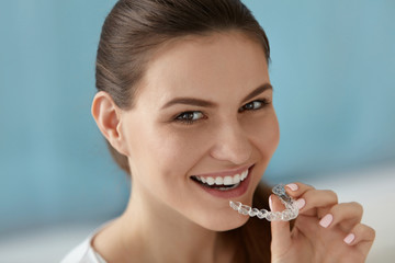 Dental care. Smiling woman using removable clear teeth braces