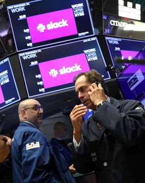 Traders work at New York Stock Exchange (NYSE) during Slack Technologies Inc. direct listing in New York