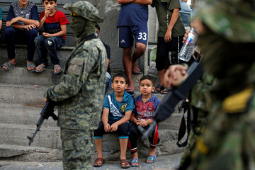 Palestinian boys look on as Islamic Jihad militants take part in an anti-Israel military show at Al-Shati refugee camp in Gaza City