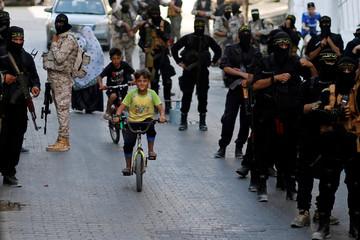 Palestinian boys ride bicycles between Islamic Jihad militants during an anti-Israel military show at Al-Shati refugee camp in Gaza City