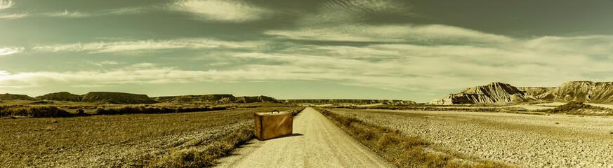 Strasse in einer Wüstenlandschaft mit Koffer