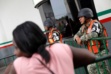 Members of the National Guard stand at the gate as migrants of different nationalities wait outside the Siglo XXI migration facility to apply for documents to legalize their stay in a country, in Tapachula