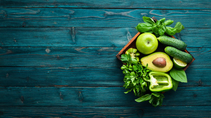 Healthy Green food. Fruits and vegetables - avocado, lime, onion, apple, kiwi, spirulina. On a blue wooden background. Top view. Free space for your text. Wall mural