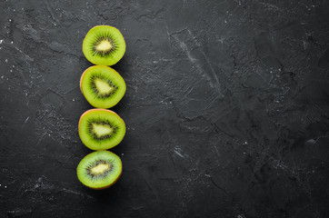 Fresh Kiwi on a black background. Top view. Free space for your text.