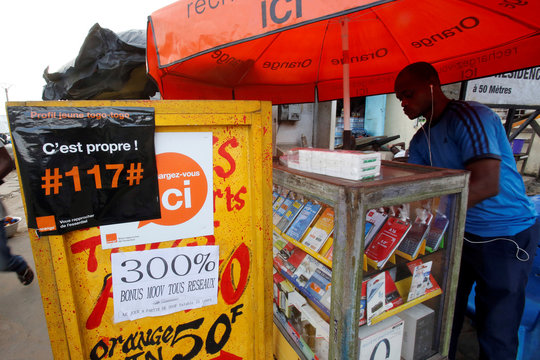 The logos of telecom company Orange are pictured at a vendor's stall in Abidjan