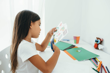 The girl cutting out of paper various pictures, children's leisure craft work